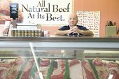 Supermarket employee standing at meat counter in supermarket