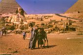 GIZA, EGYPT, CIRCA SIXTIES - vintage photo of female tourist with a camel driver, Giza, Egypt circa sixties
