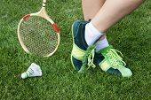 foot of woman who plays badminton on grass