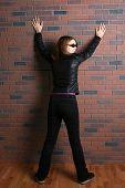 Adolescente em preto de pé com os braços e pernas se espalhou contra uma parede de tijolo