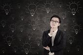 Asian Businessman Concentrating On Lightbulbs Blackboard
