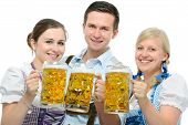 stock photo of lederhosen  - group of young people in traditional bavarian tracht holding Oktoberfest beer steins - JPG