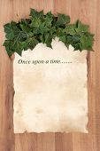 Once upon a time story phrase on old parchment with ivy over oak background.