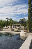 Topiary in garden with poolside sunlounger against cloudy sky