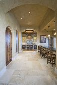Tiled floor along stools at island with arched ceiling in the kitchen