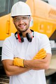 image of construction machine  - Worker at a construction site working with heavy machines  - JPG