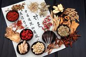 Picture of chinese herbal medicine selection with acupuncture needles and calligraphy script on rice paper.