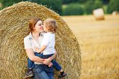 Young Mother And Her Little Son Having Fun On Yellow Hay Field