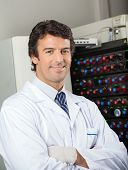 Portrait of confident male microbiologist standing by blood culture instrument in lab