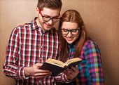 stock photo of shot glasses  - young couple in clothes and stylish hipster glasses reading a book - JPG