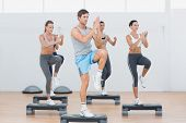 stock photo of step aerobics  - Full length of instructor with fitness class performing step aerobics exercise in gym - JPG