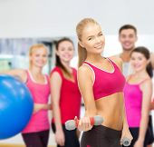 diet and fitness concept - young sporty woman with light dumbbells