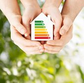 energy saving, real estate and family home concept - closeup of couple hands holding white paper hou