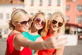 holidays, tourism and modern technology concept - smiling girls taking picture with smartphone camer