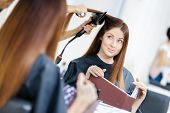 Reflection of beautician doing hair style for woman in hairdress salon. Concept of fashion and beaut