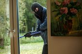 stock photo of sneak  - A burglar observing the house from behind the window