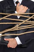 Close up of businessman handing briefcase who tied with the rope, isolated on white. Concept of slav