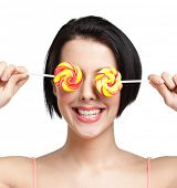 Smiley woman keeps lollypops on the eyes, isolated on white