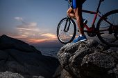 image of riding-crop  - Athlete standing with bicycle on a rock at sunset - JPG