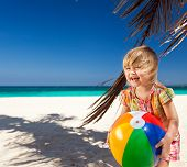 Little Girl Playing On Beach With Ball