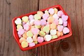 High angle view of a red rectangular candy bowl filled with Valentine's Day Candies. The heart shape