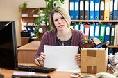 Employee, Laid Off At Work, Holding White Sheet Of Paper In Her Hands