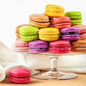 stock photo of biscuits  - traditional french colorful macarons in a glass cake stand on wooden table - JPG