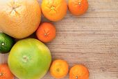 picture of crescent-shaped  - Mixed citrus fruit border over a textured wooden background with copyspace with a crescent shaped arrangement of clementines nectariines tangerines lime orange and grapefruit - JPG