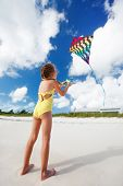 Little girl flying a kite at beach