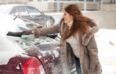 Woman cleaning car at blizzard