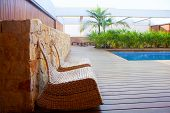 Teak wood modern house outdoor with swing chairs and palm trees pool