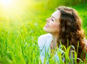 Beautiful Spring Young Woman Outdoors Enjoying Nature. Healthy Smiling Girl in Green Grass. Spring M