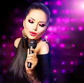 Beautiful Singing Girl. Beauty Woman with Microphone over Blinking bokeh night background. Glamour M