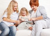 Family wiht tablet computer at sofa. Mother, grandmother and little girl at home on sofa. Generation