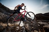 Athlete crossing rocky terrain with water barrier with his bicycle
