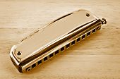 picture of wind instrument  - Old harmonica on the wooden table in vintage style - JPG