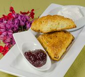 stock photo of devonshire  - scones with jam fresh cream and flowers in the background - JPG