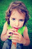 a little girls eating a popsicle in the grass done with a vintage retro instagram filter