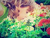 a small girl smelling some flowers done with a vintage retro instagram filter