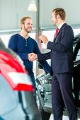 Seller or car salesman and customer in auto dealership, they shaking hands, hands over the car keys