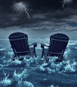 stock photo of retirement age  - Retirement crisis concept as a couple of adirondack chairs sinking in the ocean during a thunder storm as a metaphor for financial investment problems for retiring seniors who lost their savings or broken dreams symbol - JPG