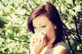 Young woman standing among blossom trees during sunny day  and wiping her nose. Girl with runny nose
