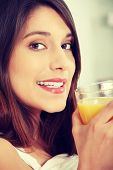 Beautiful caucasian woman in bed drinking orange juice at breakfast.