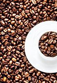 White Coffee Cup With Saucer Full Of Roasted Coffee Beans On Coffee Beans