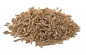 Heap of whole cumin seeds isolated on white