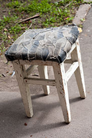 picture of scrappy  - funny old stool with scrappy bottom standing on outdoor background - JPG