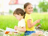 Little girl and boy are reading books while sitting on green grass