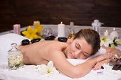 Woman having lastone therapy at spa center