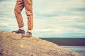 Feet Man Standing On Rocky Mountain Outdoor Travel Lifestyle Vacations Concept With Sky Clouds On Ba