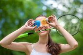 Sport Woman With Badminton Racket And Shuttlecock Near Her Eyes In The Park